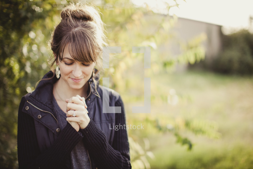 woman with her fingers laced in prayer