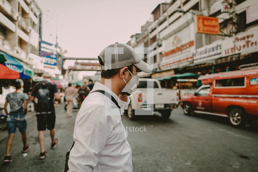 a man wearing a face mask walking on a street