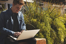 a young man sitting on a bench with laptop on his lap