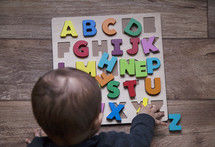 infant with an Alphabet puzzle