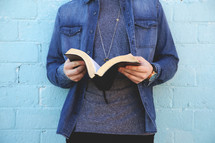 a young man standing in front of a blue wall reading a Bible