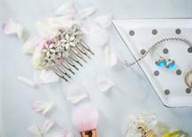 jewel studded hair comb, makeup brush, and flower petals