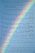 Rainbow over the bible open at Genesis.   rainbow, Noah, ark, Noah's ark, flood, Genesis, bible, open, word, words, scripture, holy book, colorfully, color, colors, sky, covenant, sign, remember, remembrance, commitment, commit, promise, promising, page, pages, inside