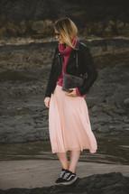 a woman walking on a rocky beach