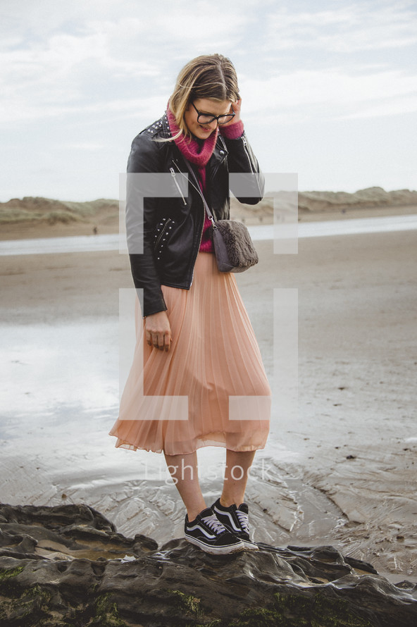 a woman in a skirt and sneakers walking on a beach