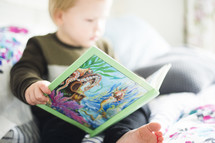 a toddler reading a children's book
