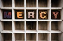 word mercy on a wood shelf