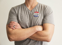 "A man with arms crossed wearing a red white and blue button reading, ""I Voted."""