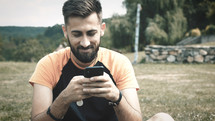 a man sitting texting on his cellphone