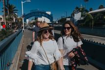 happy friends walking on a walkway by a shore