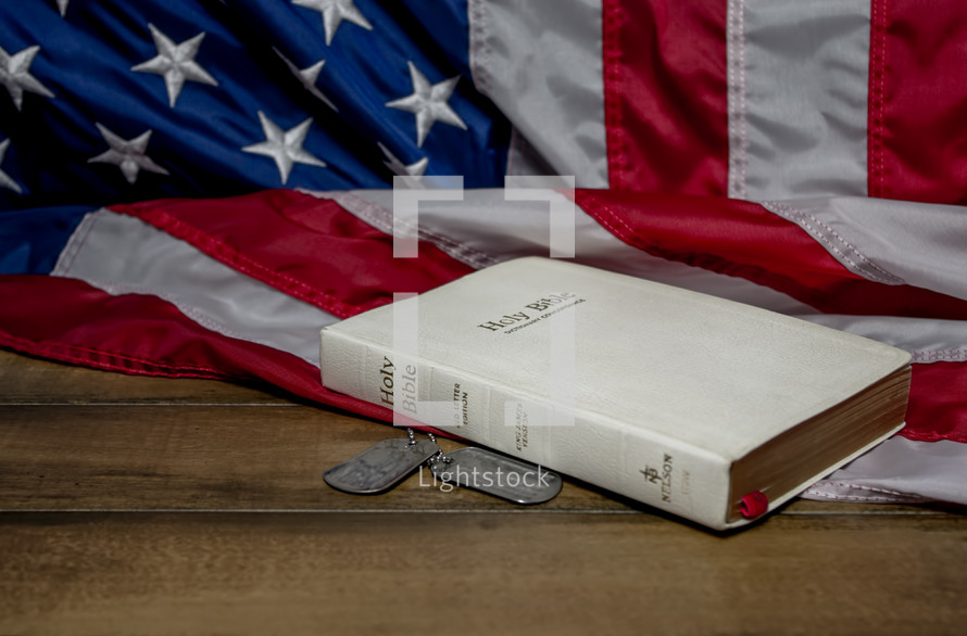 Holy Bible, American flag, and military dog tags