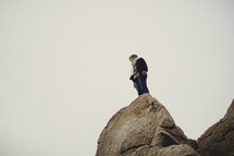 Woman standing on boulder cliff.