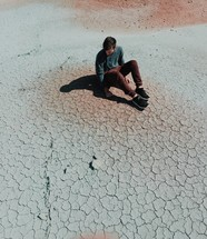 man sitting on parched soil