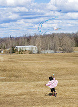 Child flying a kits in an open field.