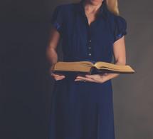 torso of a woman reading a Bible