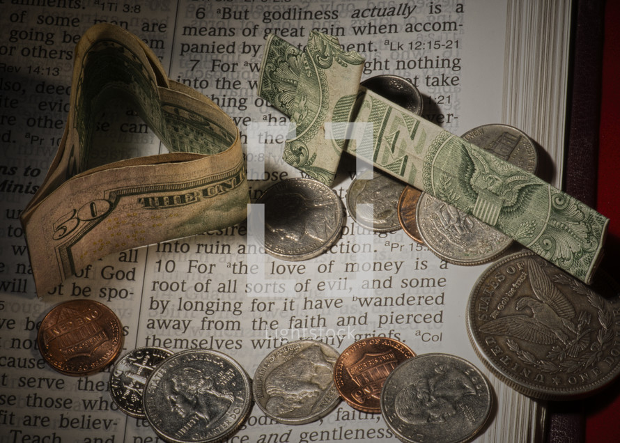 """Paper money heart and cross with coins on pages of Bible open to 1 Timothy 6:10 -- """"for the love of money."""""""