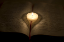 burning votive candle on a Bible