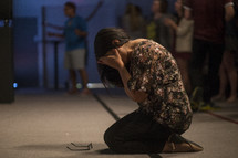 woman kneeling and in tears worshiping