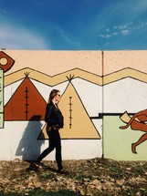 woman walking in front of a Tee Pee painting