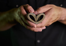 Person holding money shaped like a heart with two hands