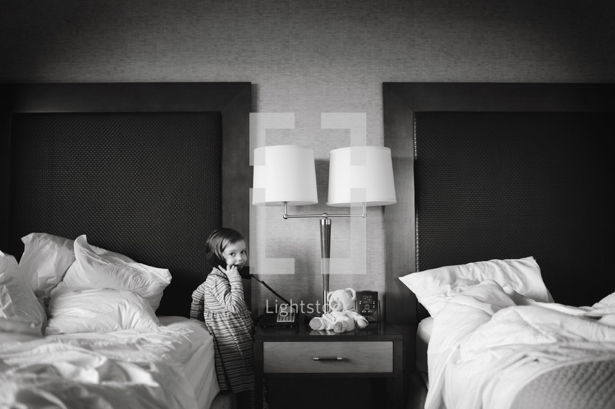 girl child on the phone in a hotel room