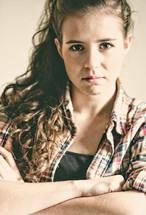 A teenage girl with arms crossed and an angry countenance.