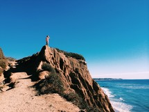 Man standing on a rocky cliff at the beach overlooking the ocean.