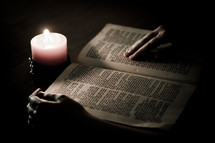 man reading a Bible with candlelight
