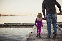 father holding hands with his daughter walking on a dock