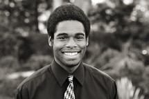 A smiling young man in a shirt and tie black African American