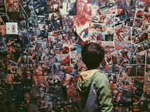 A boy looks at a wall covered in comic book pages.