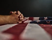 Man praying over the American Flag