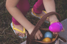 a child putting an Easter egg in a basket