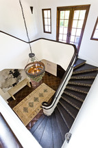 View of staircase, chandelier and foyer from upstairs spanish design decor style