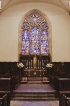 A church altar with a stained glass window in the background