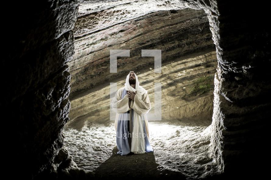 Jesus kneeling in prayer in a tomb