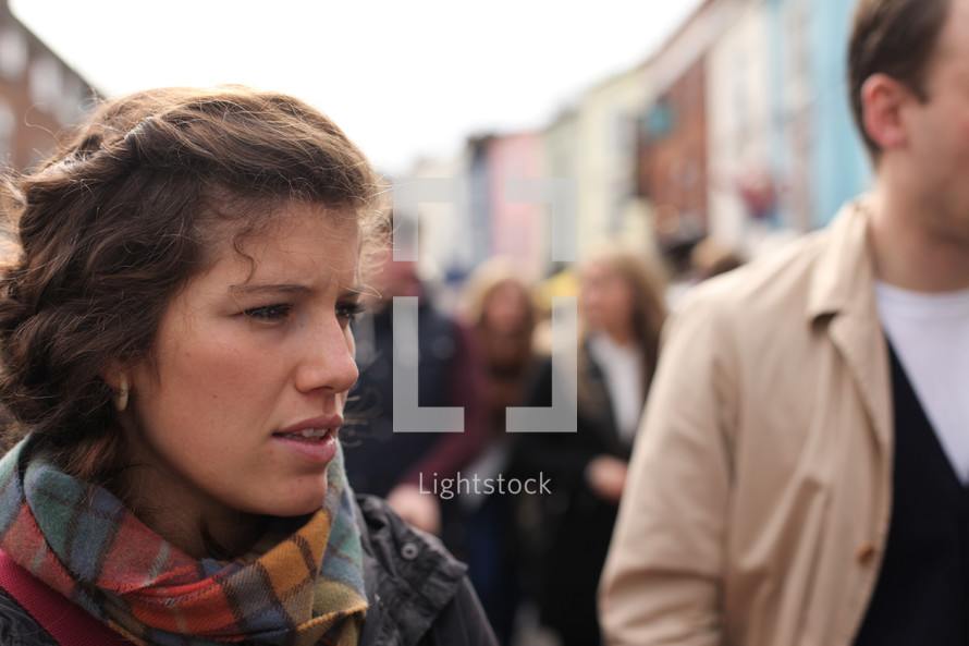 faces of people walking on a crowded sidewalk