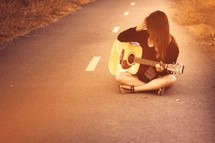 woman sitting in a road playing a guitar