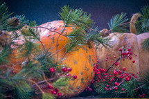 Fall Christmas decorations with berries, greenery, pumpkins and fruit