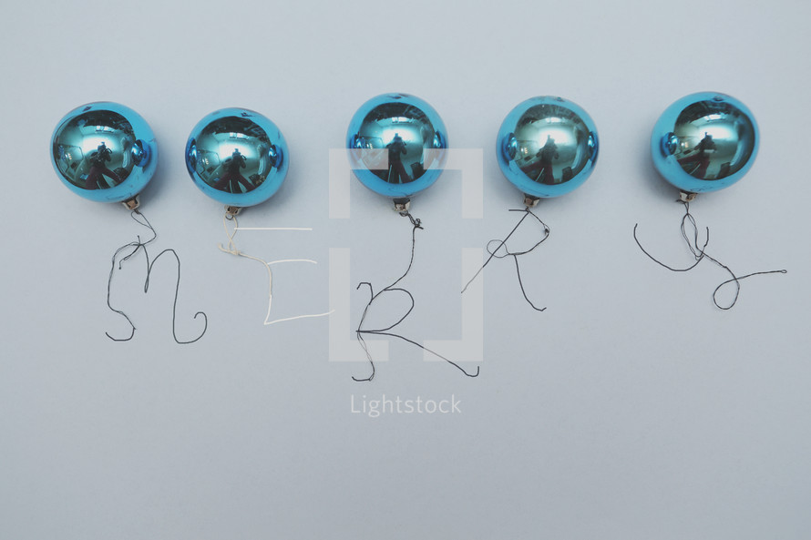 """A row of vintage blue Christmas ornaments with the word """"merry"""" written with string."""