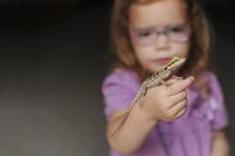 a girl holding a lizard