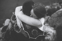 a couple wrapped in a blanket hugging outdoors