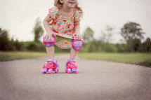 child in roller skates and knee pads
