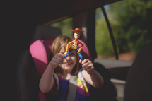 a child in a carseat holding a toy