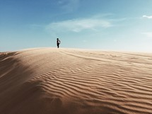 man standing at the top of a sand dune