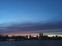 city skyline across water at night