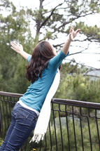 woman pretending to fly leaning over a railing