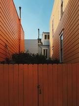 An orange gate between two orange houses.