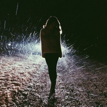 Silhouette of a woman walking on a dirt road in the rain.