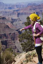 a woman pointing at a ravine from a canyon